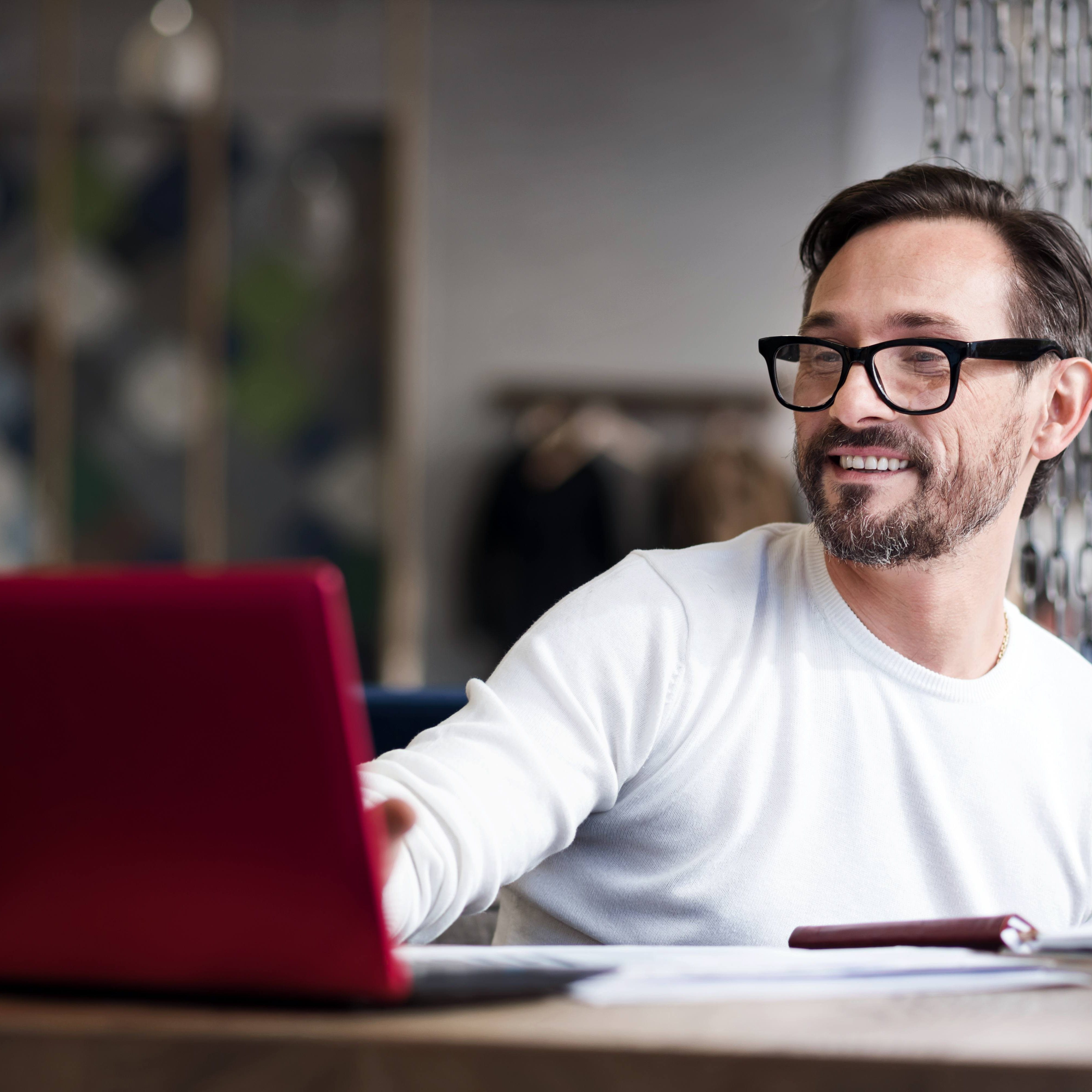 Free wifi. Cheerful bearded man wearing glasses using laptop while sitting in cafe.